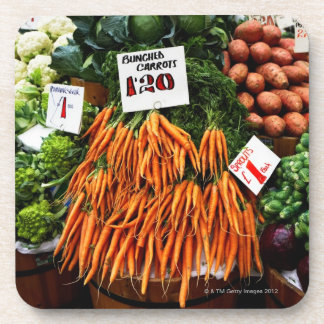 Bunches of carrots and vegetables on market coaster