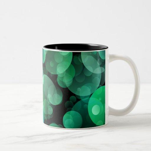 Burbujas verdes y azules del círculo sobre un taza de dos tonos