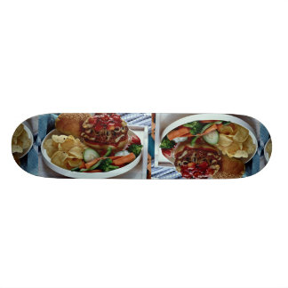 Burger , chips and vegetables in tray skateboard deck