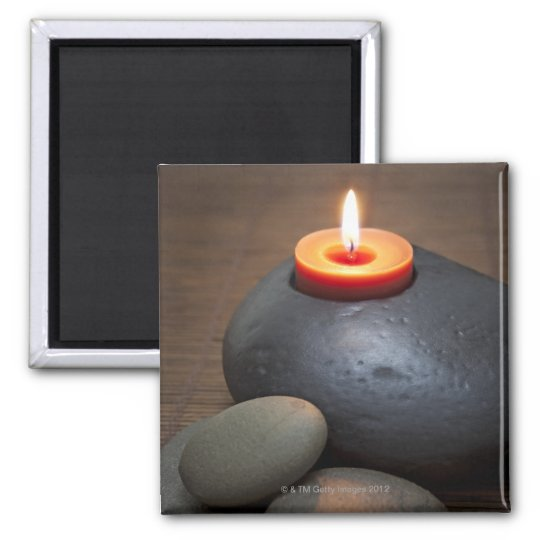 Burning candle flame with rocks in tranquil magnet