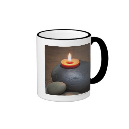 Burning candle flame with rocks in tranquil coffee mug