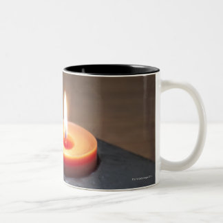 Burning candle flame with rocks in tranquil mug