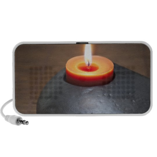 Burning candle flame with rocks in tranquil portable speaker