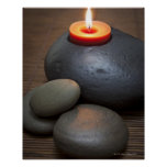Burning candle flame with rocks in tranquil posters