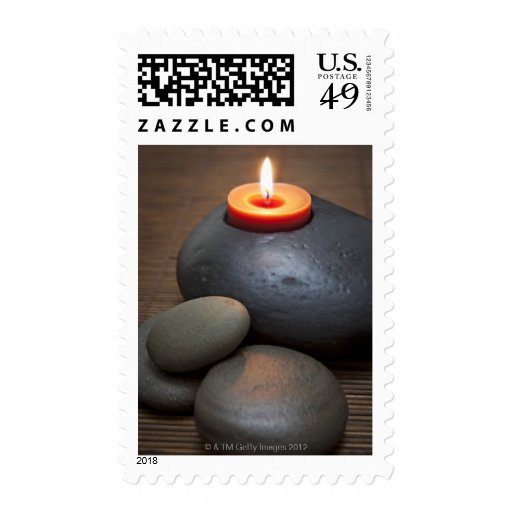 Burning candle flame with rocks in tranquil stamps