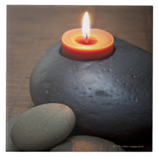 Burning candle flame with rocks in tranquil ceramic tile