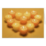 Burning candles arranged in a heart shape cards