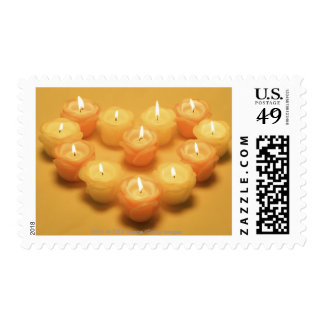 Burning candles arranged in a heart shape postage
