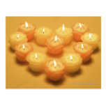 Burning candles arranged in a heart shape post cards