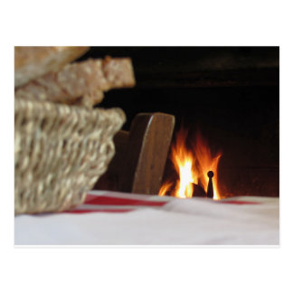 Burning fireplace with basket of bread postcard