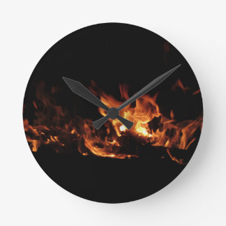 Burning fireplace with fire flames on black round clock