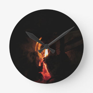 Burning fireplace with fire flames round clock