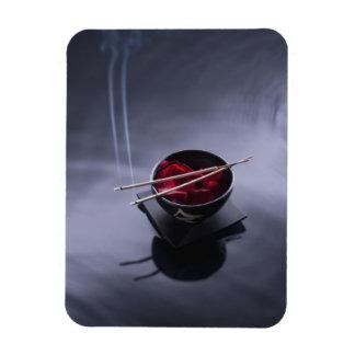 Burning incense on top of bowl of petals rectangular photo magnet