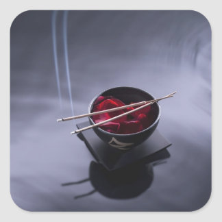 Burning incense on top of bowl of petals square sticker