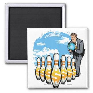 Businessman bowling a globe towards money pins magnet