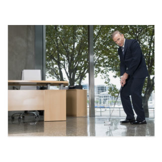 Businessman playing golf in an office postcard