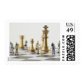 Businessmen figurines standing a top chess board postage