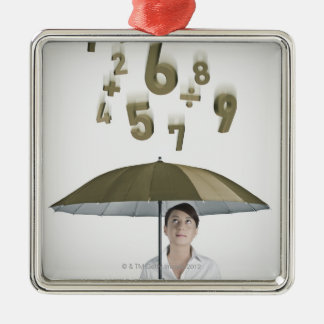Businesswoman under umbrella with numbers and metal ornament