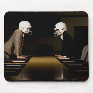 Businesswomen in face-off wearing football mouse pad