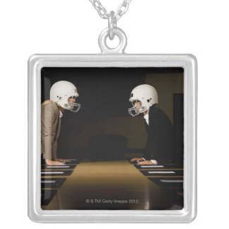 Businesswomen in face-off wearing football silver plated necklace