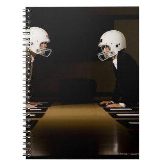 Businesswomen in face-off wearing football spiral notebook