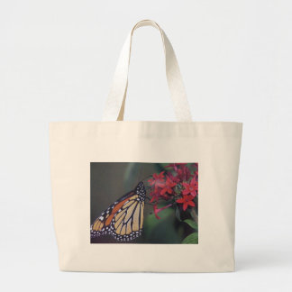 butterfly flying around red flower large tote bag