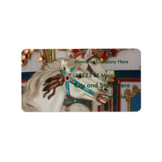 Caballo blanco del carrusel con la imagen azul del etiquetas de dirección