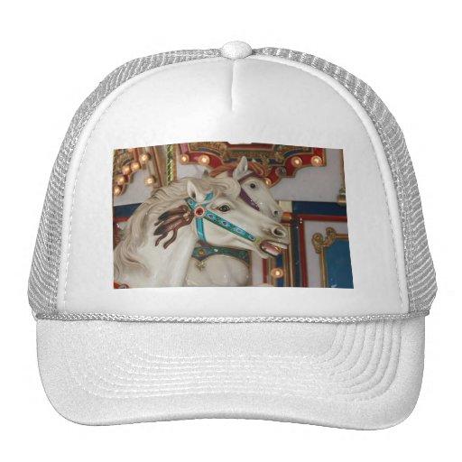 Caballo blanco del carrusel con la imagen azul del gorras