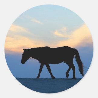 Caballo de la playa de la puesta del sol etiqueta redonda