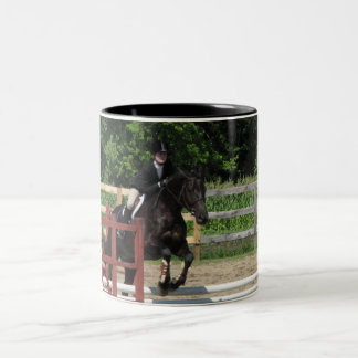 Caballo negro que salta en una taza