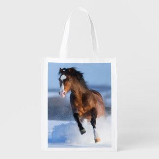 Caballo que corre a través del campo en invierno bolsa de la compra