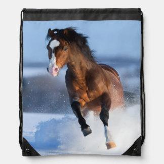 Caballo que corre a través del campo en invierno mochilas