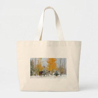 Caballos en nieve con el árbol coloreado bolsas
