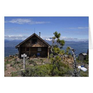 Cabaña de madera en mota negra tarjeta de felicitación