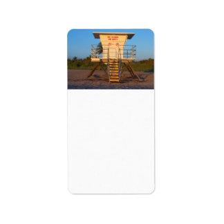 Cabaña del salvavidas en imagen de la playa de la  etiqueta de dirección