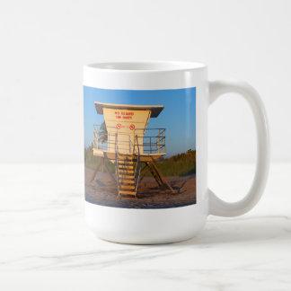 Cabaña del salvavidas en imagen de la playa de la taza básica blanca