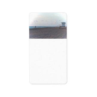 cabaña del salvavidas en la playa con el caminante etiqueta de dirección