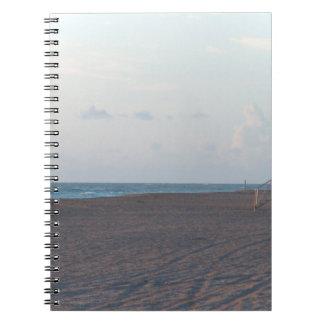 cabaña del salvavidas en la playa con el caminante libros de apuntes con espiral
