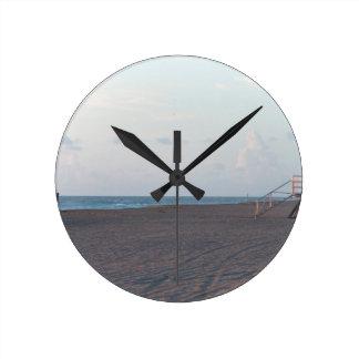 cabaña del salvavidas en la playa con el caminante reloj redondo mediano