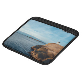 Cabin on stone cliff at shore of an ocean iPad sleeves