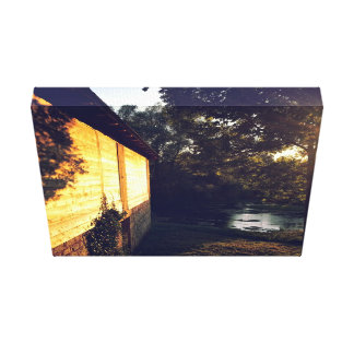 Cabin with wooden shingles next to pond canvas print