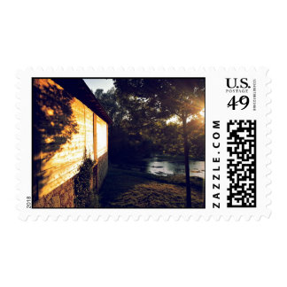Cabin with wooden shingles next to pond postage stamp