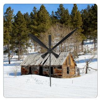 Cabina vieja del invierno reloj cuadrado