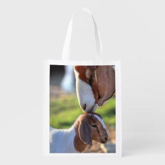 Cabra de la madre que besa a su bebé en la cabeza bolsas de la compra