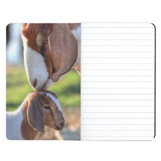 Cabra de la madre que besa a su bebé en la cabeza cuaderno