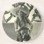 "Cactus Kate Drink Coaster<br><div class=""desc"">Vintage photo of a cute young blond wearing very big cowboy hat,  black and white cowhide chaps,  holster and holding a gun</div>"
