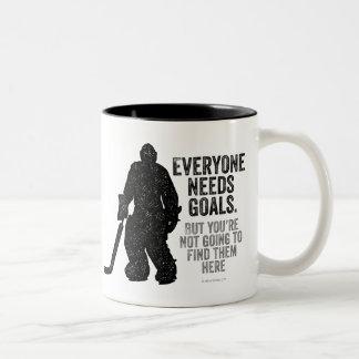 Cada uno necesita las metas (el hockey) taza de café de dos colores