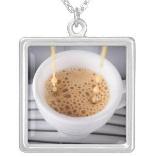 Café express que vierte en la taza colgante cuadrado