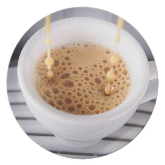 Café express que vierte en la taza platos