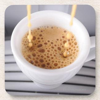 Café express que vierte en la taza posavasos